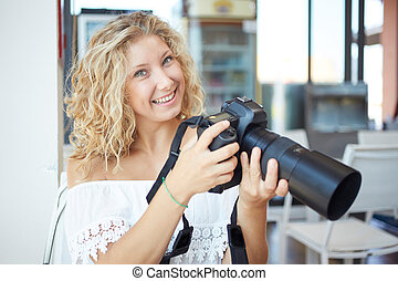 young woman tourist with camera in her hands