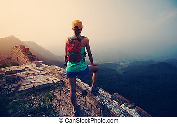 young woman trail runner have a rest at great wall on the top of mountain
