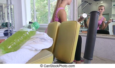 Young woman training in fitness club doing dumbbell exercise in front of mirror