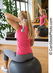 Young woman training in gym with dumbbells in front of a mirror sitting on fitball