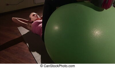 Young woman training in health club doing abs exercise with fitness ball