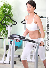 young woman training on a treadmill in the gym