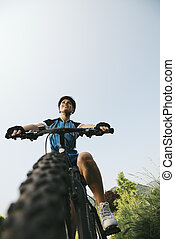 young woman training on mountain bike and cycling in park. ...