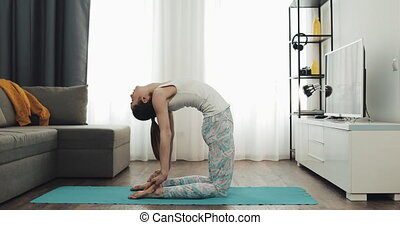 Young woman training yoga at home sitting on mat and stretching muscles of legs. Healthy and sport lifestyle.