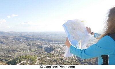 Young woman traveler with a backpack and a map