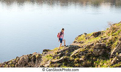Young Woman Traveler with Backpack Climbing on Beautiful Rock at Warm Sunny Evening. Travel and Adventure Concept.