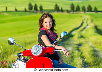 Young woman traveling by a scooter - Young beautiful woman...