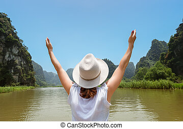 woman traveling by boat among the islands with arms up feeling free bliss