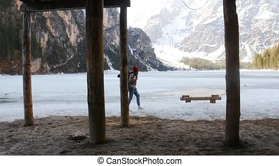 Young woman traveling on a lago di braies coast with a big...