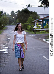Young woman travels in tropical town.