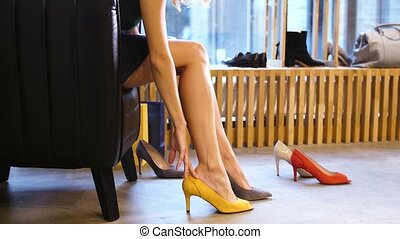 young woman trying heeled shoes at store