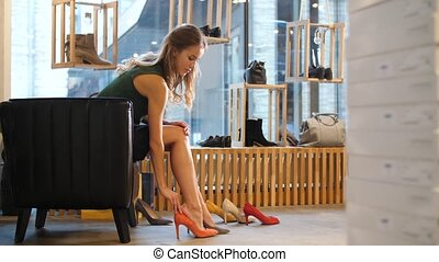 young woman trying heeled shoes at store - sale, shopping,...
