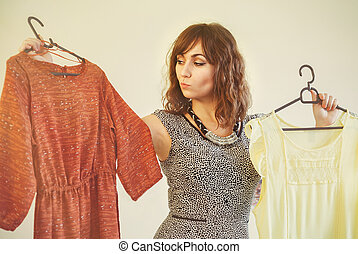 Young woman trying to choose a dress to wear