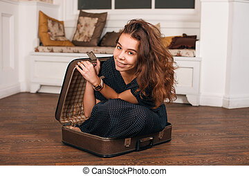 Young woman trying to climb into a suitcase.