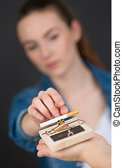 young woman trying to get cigarette on mouse trap