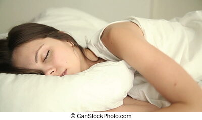 Young woman turning and tossing in her sleep - Young...