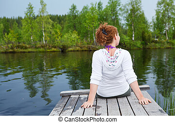 Young woman turning back sitting on wooden boards on pond edge