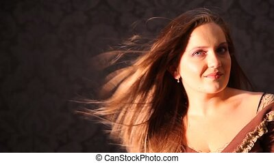 young woman turning head with hair fluttering in wind