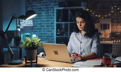 Young woman turning off laptop and light in office at night...