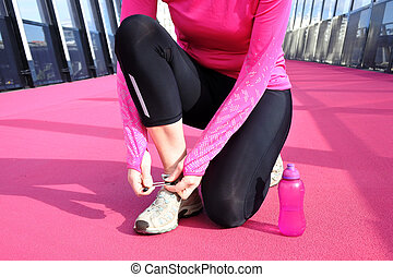 Young woman tying her shoelaces on a bright pink road