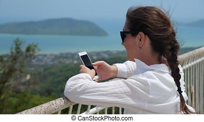 young woman types on phone leaning on viewpoint handrails - ...