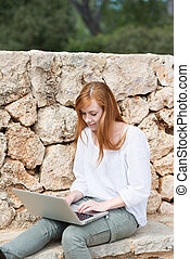 Young woman typing on her laptop keyboard