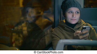 Young woman typing sms during bus ride