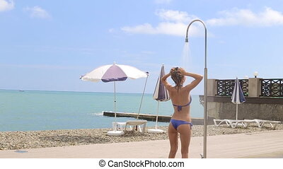 Young Woman Under Shower at the Summer Beach