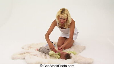 Young Woman Undressing Her Small Baby Boy Sitting On The Floor