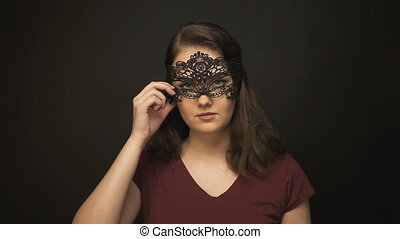 Young woman undressing lace mask on dark background