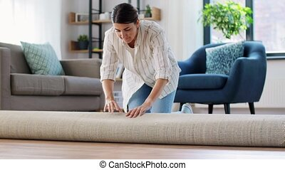 young woman unfolding carpet at home - household, home ...