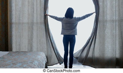 Young woman unveil curtain and looking out of window and a child runs up to her. Hotel