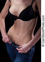 Young woman unzips pants - Young woman in black bra unzips...
