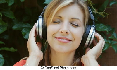 Young woman. Upbeat headphones. - A young woman closes her...