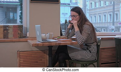 Young woman use laptop while eat sandwich in the cafe at business lunch