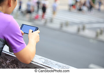 young woman use smart phone in city