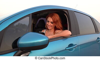 Young woman uses a mobile phone in her car