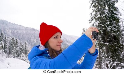 Young woman uses a smartphone for make a photos of a...