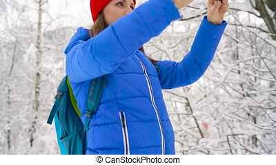 Young woman uses a smartphone for make selfie photos on the background of a beautiful view in the mountains, Carpathians