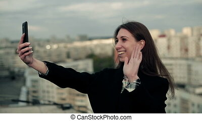 Young woman uses a smartphone on the roof