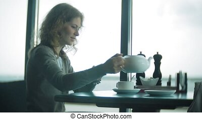 Young woman uses a tablet and phone, drinks tea in a cafe bar