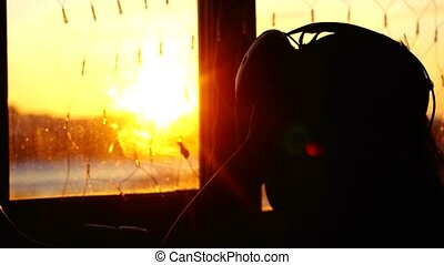 Young woman uses a virtual reality glasses at home during sunset with city background from the window and beautiful lense flare effects. 3840x2160 4k