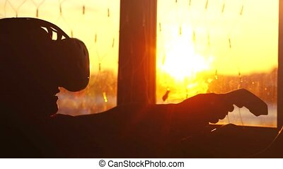 Young woman uses a virtual reality glasses at home during sunset with city background from the window and beautiful lense flare effects.