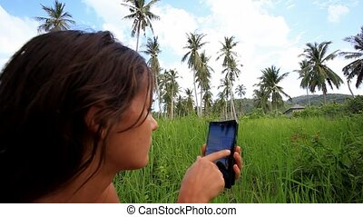 Young  woman uses mobile phone. Jungle in Koh Samui, Thailand. HD. 1920x1080