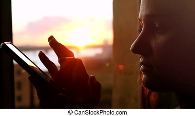 Young woman uses the phone, standing at the window drinking coffee on the background of a beautiful sunset with sun flare.