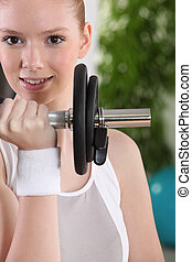 Young woman using a barbell