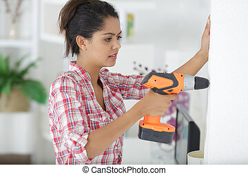 young woman using a drill