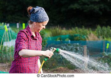 Young woman using a garden hose nozzle