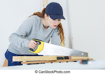 young woman using a hand saw in a woodshop