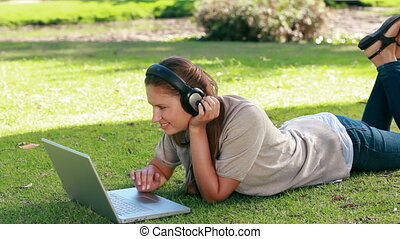 Young woman using a laptop in a park